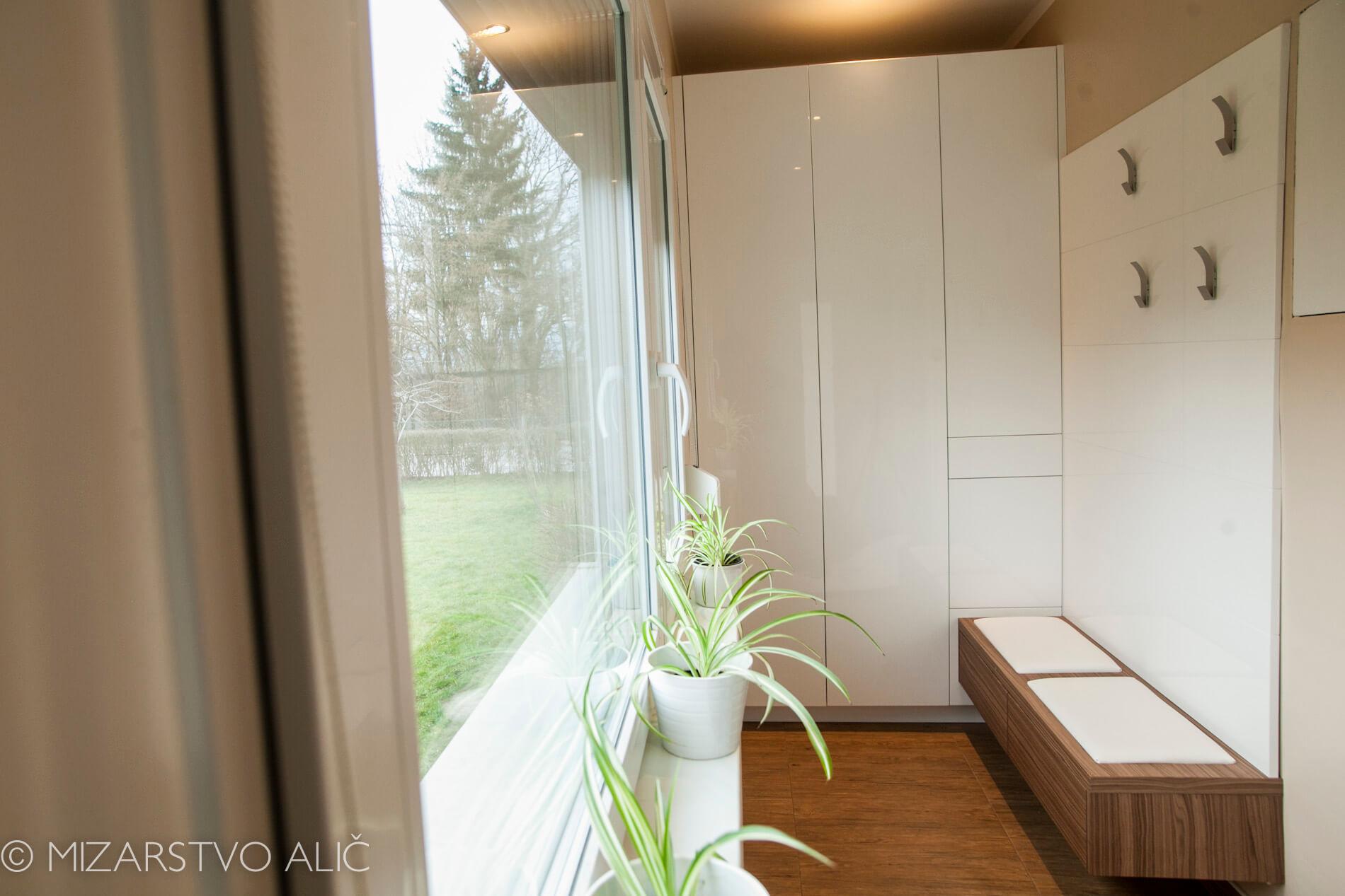 bela vgradna garderobna omara, predalnik in stena z obešalniki