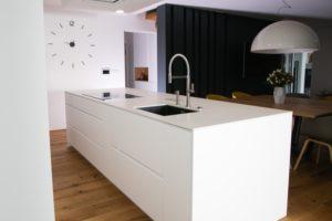 bela kuhinja z otokom pult umetni kamen bel